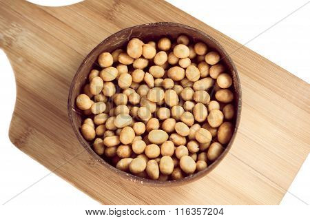 Peanuts In Glaze Shell In A Round Plate On A Cutting Board Isolated