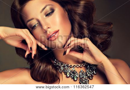 Beautiful model girl brunette with large necklace on the neck