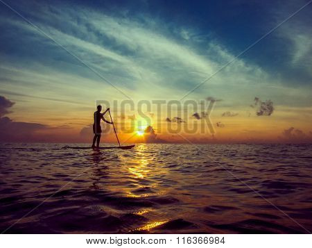 Young man paddle boarding during a beautiful sunrise in Mexico