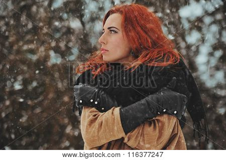 Young sadly woman in snow