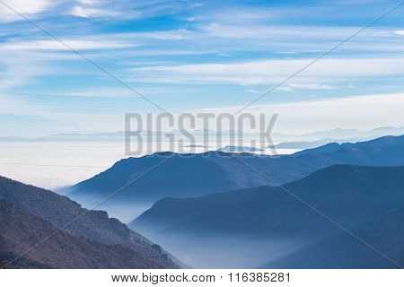 Blue Toned Mountain Silhouette And Foggy Valleys In Winter