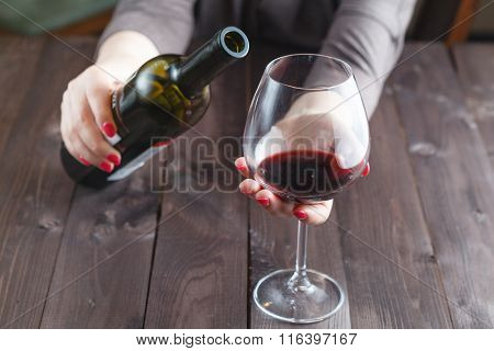 Alcoholic Woman Is Pouring Wine Into A Glass