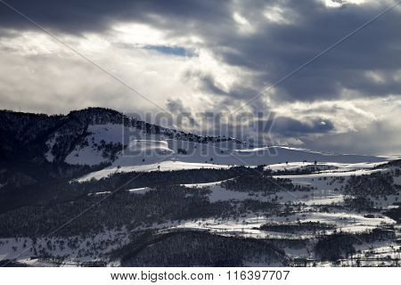 Village In Winter Mountains And Storm Clouds At Evening