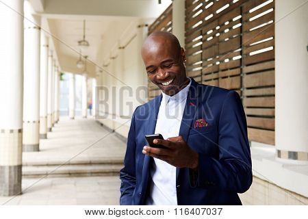 Happy Older African Businessman With Cell Phone