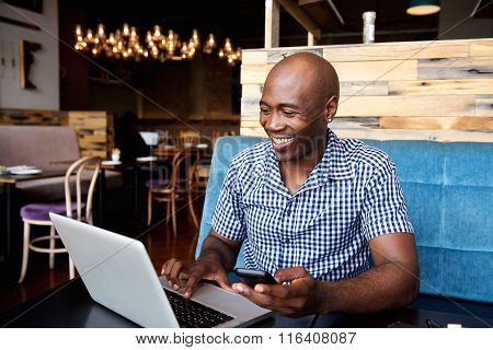 Smiling Man With A Mobile Phone Sitting At Cafe Using Laptop