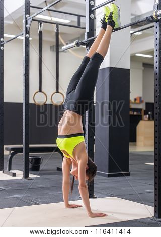 Fit woman doing handstand Athlete standing on hands Concept balance sport fitness.