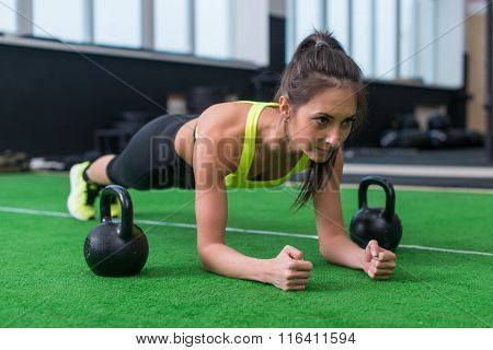 Fit woman doing plank exercise working on abdominal muscles in the gym