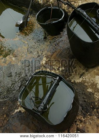 Heavy oil pollution pollutes earth and water at an illegal oil field in Java, Indonesia