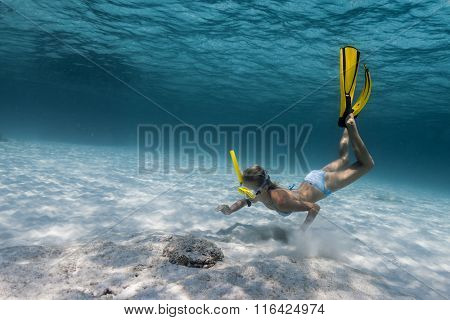 Underwater shot of the lady exploring sandy bottom in a tropical sea