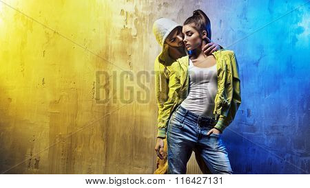 Young fashionable couple on a concrete wall background