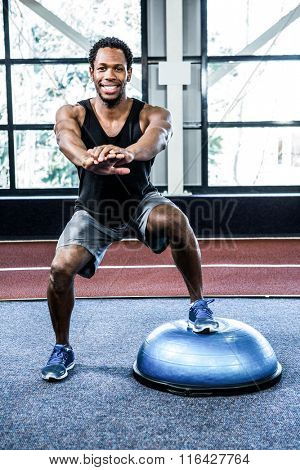 Fit man doing exercise with bosu ball in crossfit
