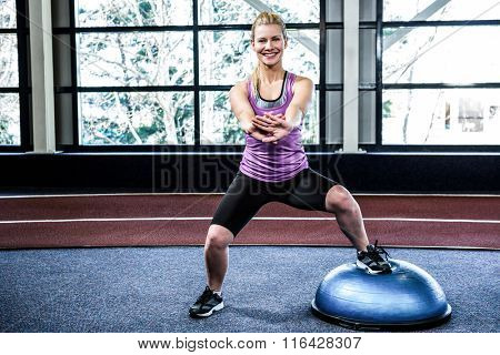 Fit woman doing exercise with bosu ball in crossfit