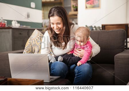 Young Mom Working At Home With Her Baby