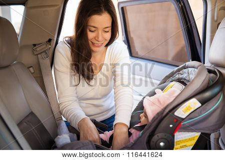Young Mom Securing A Child Car Seat