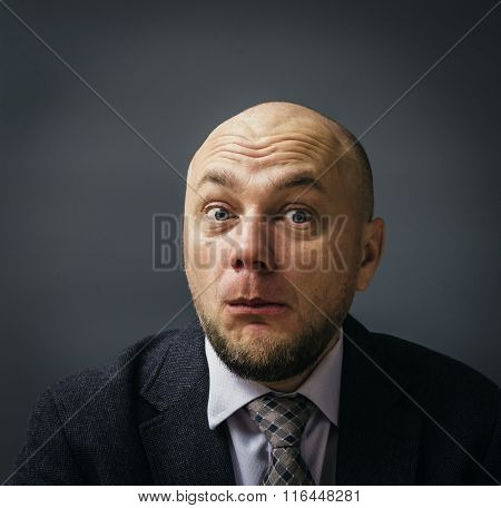 Portrait of an adult man in a business suit on a black background. Surprise astonished man.