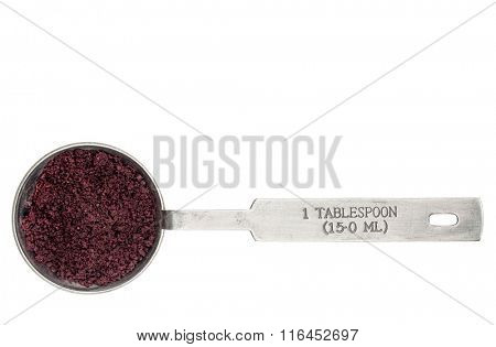 acai berry powder in a metal measuring tablespoon isolated on white