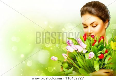 Beautiful girl with a Bouquet of colorful Tulip flowers. Beauty Woman with Spring Flower bunch. Happy surprised model woman smelling flowers. Mother's Day gift. Valentine's Day. Springtime