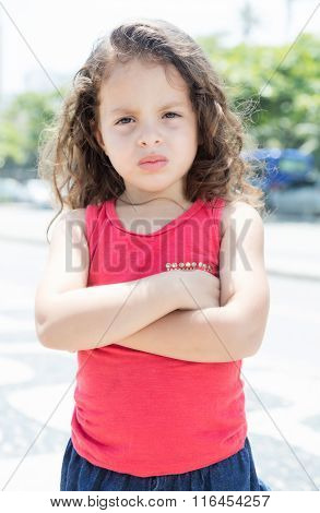Courageous Child In A Red Shirt Outside Looking At Camera