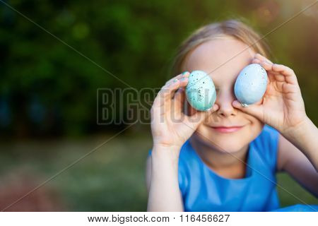 Adorable playful little girl with colorful Easter eggs outdoors at spring
