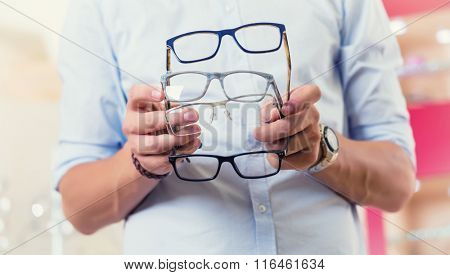 Man at optician or optometrist buying glasses