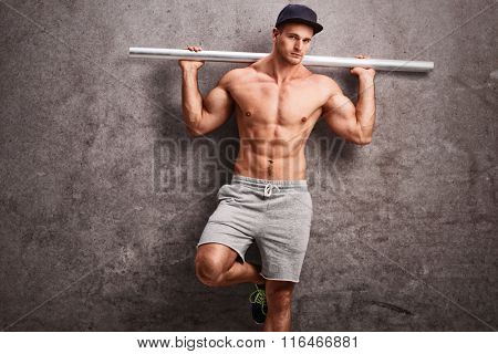 Young shirtless guy holding a metal pipe and leaning against a gray concrete wall