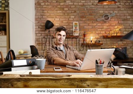 Young man sitting at desk, working with laptop computer, looking at camera.