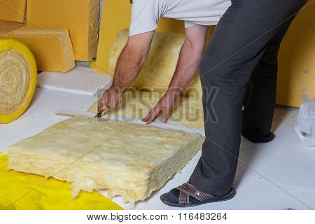 Handyman Cutting The Termal Insulation At The Attic