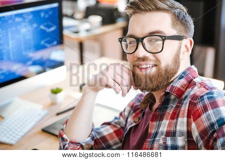 Happy attractive young man with beard in glasses working and designing project on his computer