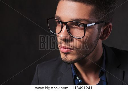 portrait of smart man wearing glasses in dark studio background while looking away from the camera