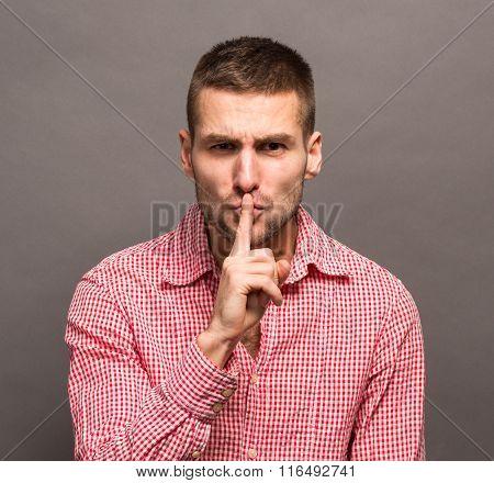 Man making a shushing gesture