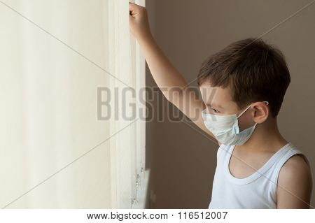 kid standing at the window in the hospital in medical mask