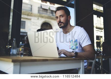 Young man coffee shop owner using net-book and monitors the work of his personnel