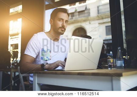 Successful businessman working on laptop computer during work break in luxury coffee shop
