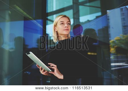 Young businesswoman look away while reading information on digital touch pad
