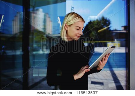 Woman employee searching information on touch pad about client before meeting with him