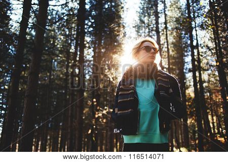 Woman tourist enjoying fresh air while resting after strolling in forest in sunny autumn day