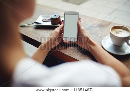 Young female reading news via cell telephone while sitting in coffee shop