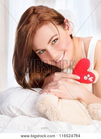 Closeup portrait of cute young girl lying down in her bed at home, receive soft bear toy with red heart as gift for Valentine day