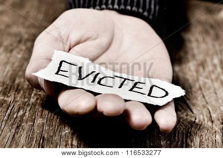 closeup of a piece of paper with the word evicted in the hand of a caucasian man