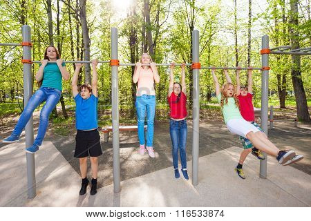 Friends chin up on the playground together
