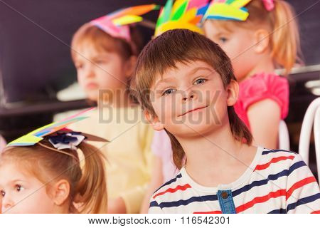 Portrait of smiling surprised little boy in class