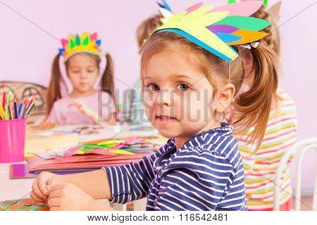Girl in handmade headwear glue paper to cardboard