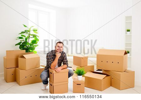 Moving To A New Apartment. Happy Man With Cardboard Boxes