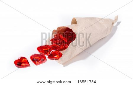Red Glass Hearts Are Poured Out From A Paper Parcel