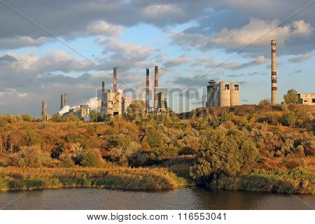The Plants On The Banks Of The Picturesque River Surrounded By Autumn Forest. Factory Pipe Smoke And