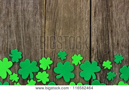 St Patricks Day bottom border of shamrocks over rustic wood