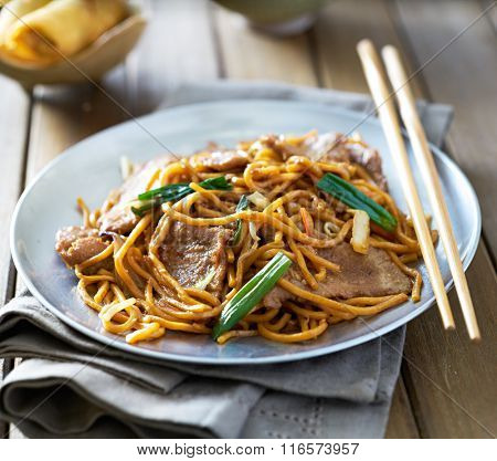 chinese food - beef lo mein on a plate with chopsticks