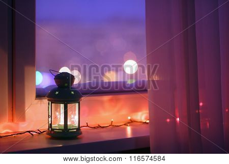 Lantern with candle on a window sill with Christmas lights