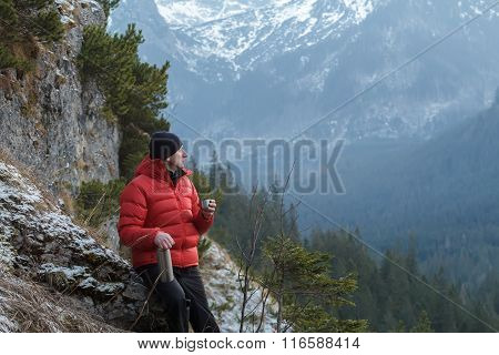 Well built young man relaxing drinking hot drink and holding metal vacuum flask