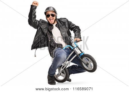 Joyful biker riding a small childish bicycle and gesturing with his hand isolated on white background
